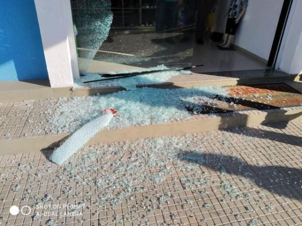Loja tem a porta de vidro atingida pelos disparos.(Imagem:Divulgação)