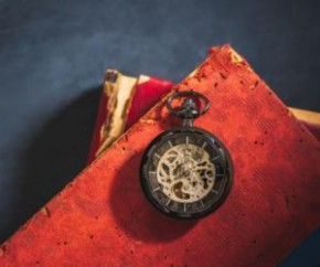 Relógio de bolso e livro velho no chão de cimento.(Imagem:Divulgação)