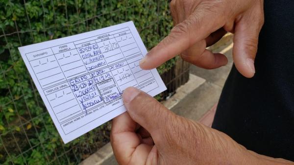Pessoa vacinada mostra cartão com aplicação de duas doses de imunizante.(Imagem:Danilo Girundi)